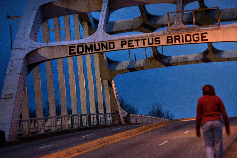 A woman walks across the Edmund Pettus Bridge, on March 4, 2015 in Selma, Alabama ahead of the 50th anniversary of a seminal moment in America's democracy when some 600 rights activists were attacked by police with clubs and tear gas at the bridge (AFP Photo/Brendan Smialowski)