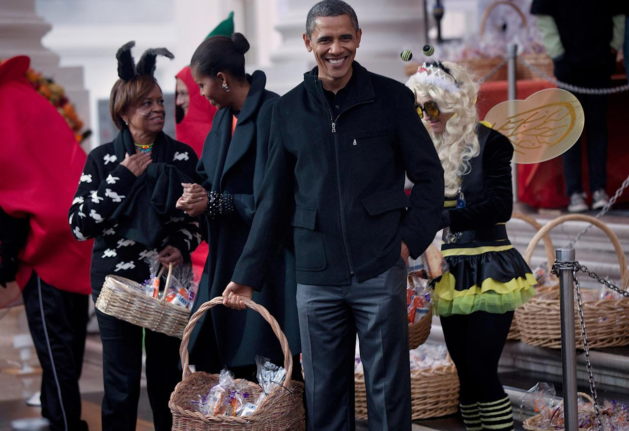 WASHINGTON - OCTOBER 29:  U.S. President Barack Obama waits with first lady Michelle Obama and her mother Marian Robinson to greet trick or treaters at the White House October 29, 2011 in Washington, DC.  President Barack Obama and first lady Michelle Obama hosted military families and other trick or treaters for a Halloween party.  (Photo by Brendan Smialowski/Getty Images)