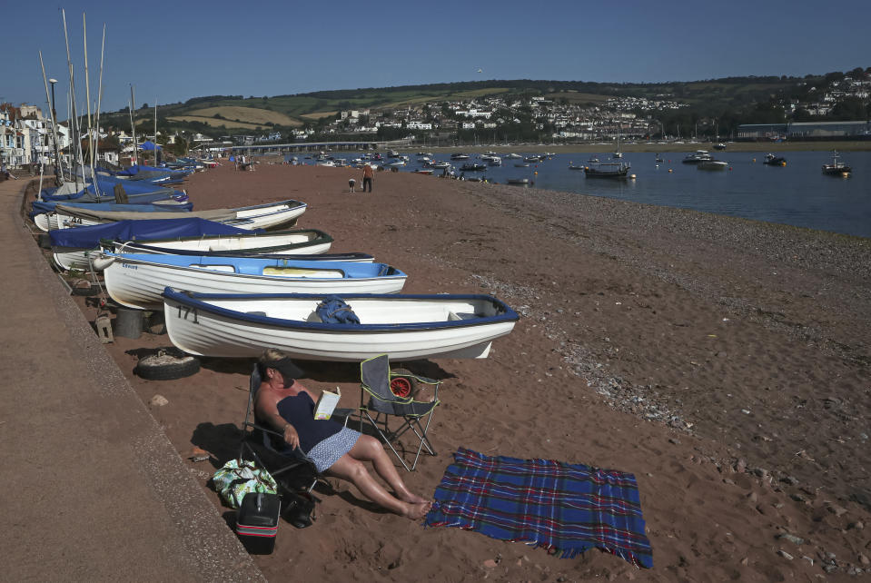 A woman reads a book as she sunbathes on the beach in Shaldon, Devon, England, Sunday July 18, 2021. Visiting the fishing village of Shaldon a small cluster of mainly Georgian houses and shops at the mouth of the River Teign, is like stepping back into a bygone era. It features simple pleasures that hark back to analog, unplugged summer days: a book and a picnic blanket, a bucket and spade, fish and chips. (AP Photo/Tony Hicks)