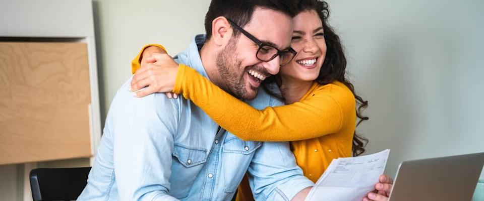 Happy couple, woman hugging man, looking at bills, sitting at desk in front of laptop