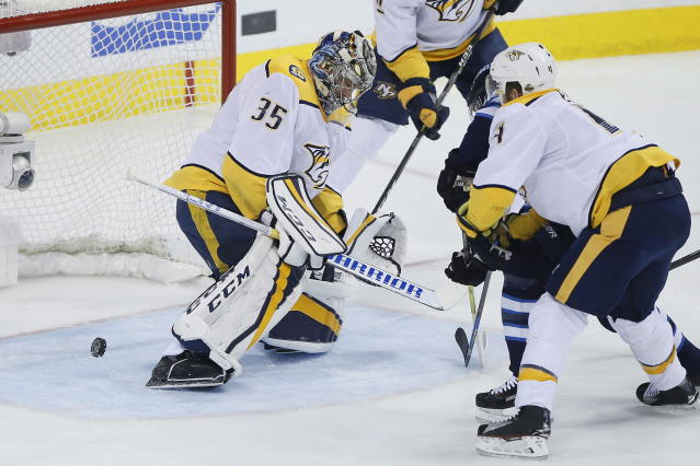 A shot by Winnipeg Jets' Bryan Little trickles through the pads of Nashville Predators goaltender Pekka Rinne (35) but wide of the net during the first period of Game 4 of an NHL hockey second-round playoff series in Winnipeg, Manitoba, Thursday, May 3, 2018. (John Woods/The Canadian Press via AP)
