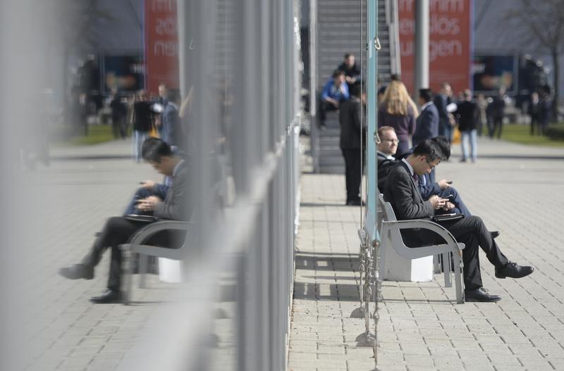 Visitors check their smartphones at the world's biggest computer and software fair CeBit in Hanover