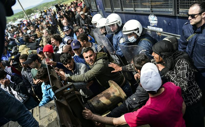 Refugees and migrants attempt to break through a police barricade as they protest to call for the reopening of the border in the village of Idomeni, on April 11, 2016 (AFP Photo/Bulent Kilic)