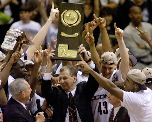 University of Connecticut head coach Jim Calhoun holds the NCAA national championship trophy high after his team defeated Duke University 77-74, March 29. The Huskies won their first-ever NCAA national championship at Tropicana Field in St. Petersburg. At right is Huskies' center Jake Voskuhl (43). JLS/HB/JDP