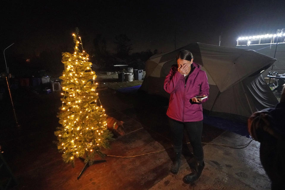 Cristin Trahan wipes tears after Tiffany Theriot, founder of the charity Cajun Commissary, surprised her with a Christmas tree donated by a volunteer, on the property of their destroyed home in Lake Charles, La., Friday, Dec. 4, 2020. Cristin, her husband and a son are living in tents on the property, while her other son, his fiancée and their one-year old son are living in a loaned camper there. A relative's home on the same property is now gutted and they are living in a camper as well. (AP Photo/Gerald Herbert)