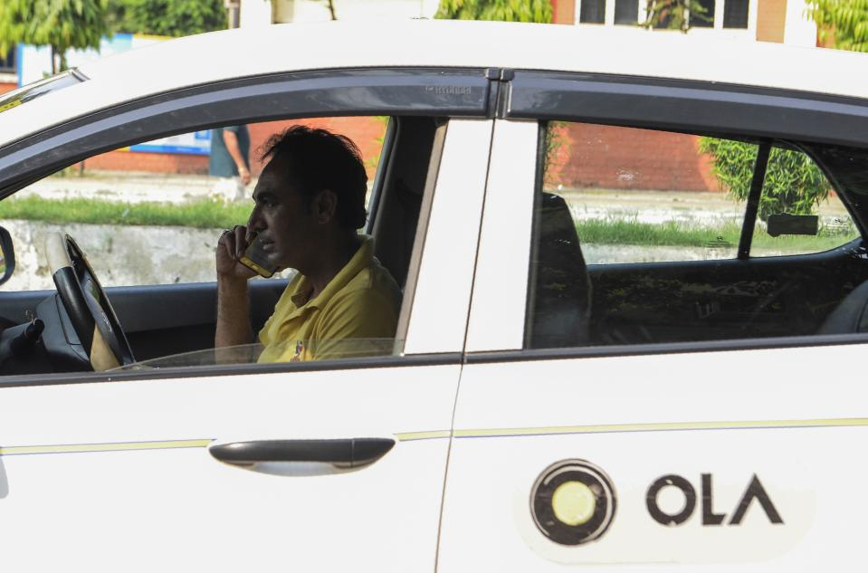In this photograph taken on September 12, 2019, an Ola cab driver talks on his mobile phone at a roadside in Amritsar. - When India's Finance Minister Nirmala Sitharaman September 10 claimed millennials' preference for ride-hailing apps was contributing to a painful slump in car sales, it sparked a online backlash from furious youngsters. While data shows ride-hailing firms such as Uber and Ola are popular with younger consumers more comfortable with shared mobility and digital trends, analysts say the auto industry's problems run deeper than that -- and it is facing more serious bumps in the road. (Photo by NARINDER NANU / AFP) / TO GO WITH 'INDIA-TRANSPORT-AUTOMOBILE-ECONOMY', FOCUS BYGLENDA KWEK WITH ARCHANA THIYAGARAJAN        (Photo credit should read NARINDER NANU/AFP via Getty Images)