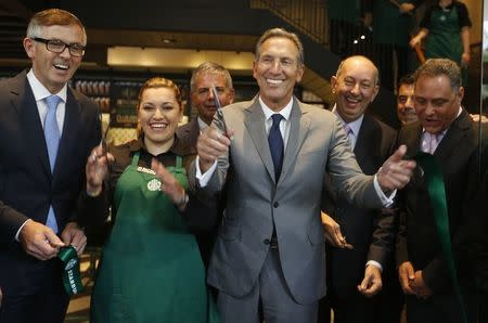 CEO of Starbucks Howard Schultz (C) smiles after inaugurating the coffee chain's first Colombian store at 93 park in Bogota July 16, 2014. REUTERS/John Vizcaino