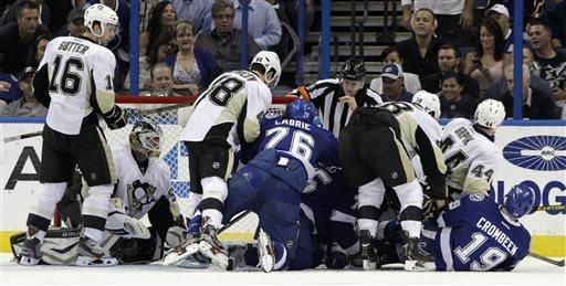 Tampa Bay Lightning and Pittsburgh Penguins players dive for the puck in front of goalie Tomas Vokoun, of the Czech Republic, second from left, during the first period of an NHL hockey game, Thursday, April 11, 2013, in Tampa, Fla. (AP Photo/Chris O'Meara)