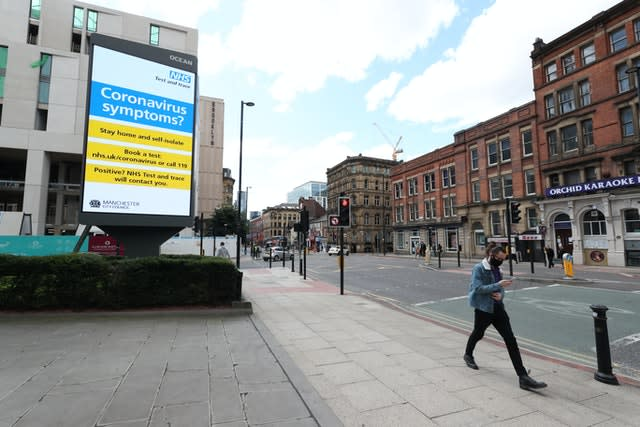 A person wearing a mask walks past coronavirus advertising in Manchester (Peter Byrne/PA)