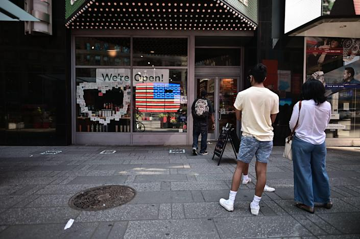 The American flag is reflected in a Cafe as people queue for coffee at Times Square as New York City enters phase two of reopening June 22, 2020. (Photo: JOHANNES EISELE/AFP via Getty Images)