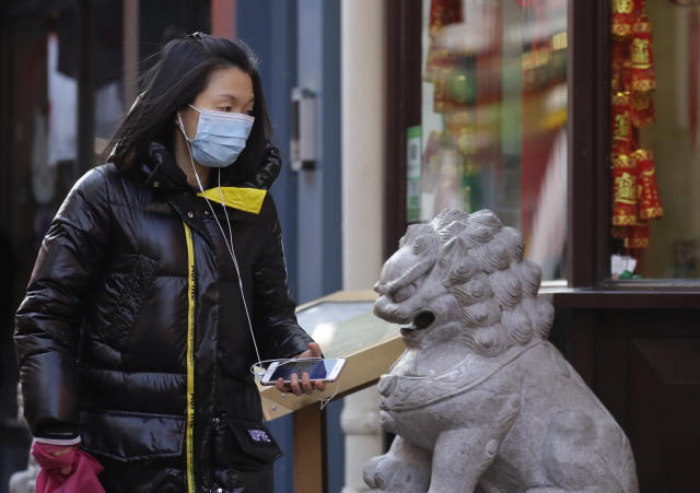 A woman wears a mask as she walks through China Town in London last week. (Kirsty Wigglesworth/AP)