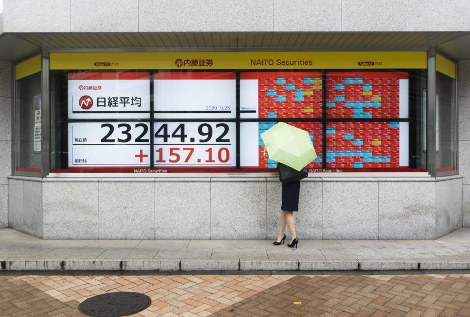 A woman looks at screens showing Japan's Nikkei 225 index at a securities firm in Tokyo on Friday, Sept. 25, 2020. Asian shares advanced Friday, cheered by a modest rally on Wall Street and rising hopes for fresh stimulus for the U.S. economy.(AP Photo/Hiro Komae)