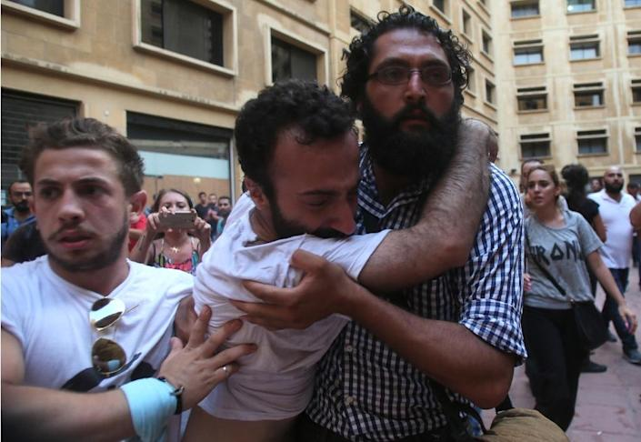 Lebanese activist Lucien Abou Rjeily (C) is carried by fellow demonstrators after activists claim he was beaten by Lebanese police (AFP Photo/)