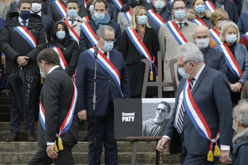 French lawmakers gather to pay homage to slain teacher Samuel Paty, Tuesday, Oct. 20, 2020 on the steps of the National Assembly in Paris. A memorial march will be held Tuesday evening near Paris in homage to the history teacher who was beheaded last week, while French police said 16 people remain in custody as part of the investigation into the attack. (AP Photo/Lewis Joly)