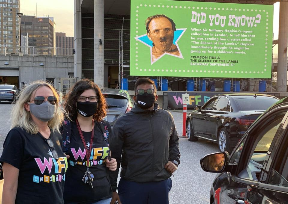 Four people standing in masks outdoors.