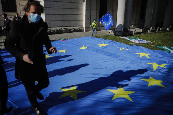 FILE - in this Wednesday, April 22, 2020 file photo, a man with a face mask and a child with an European flag attend an event of the Pulse of Europe movement to collect signatures for more support for Italy during the coronavirus and the COVID-19 outbreak in front of the Italian embassy in Berlin, Germany. European Union leaders are preparing for a new virtual summit, which will take place Thursday, April 23, 2020, to take stock of the damage the coronavirus has inflicted on the lives and livelihoods of the bloc's citizens and to thrash out a more robust plan to revive their ravaged economies. (AP Photo/Markus Schreiber, File)