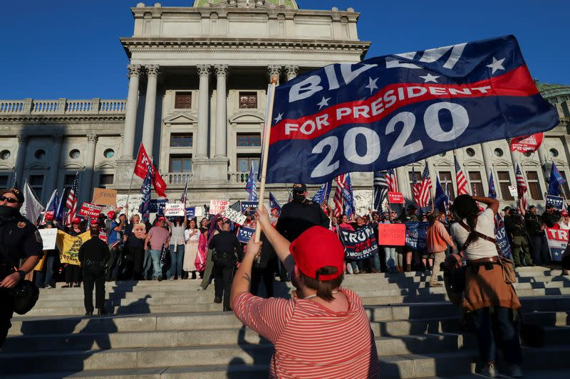 FILE PHOTO: Supporters of U.S. President Donald Trump rally as a supporter of Democratic presidential nominee Joe Biden celebrates outside the State Capitol building after news media declared Biden to be the winner of the 2020 U.S. presidential election, in Harrisburg