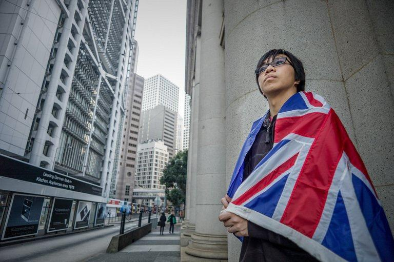 Danny Chan wrappened in a colonial era flag in Hong Kong on Thursday. Sixteen years after Hong Kong returned to Chinese rule, public discontent with Beijing is swelling and protesters have been rallying around an unexpected symbol -- the British colonial flag