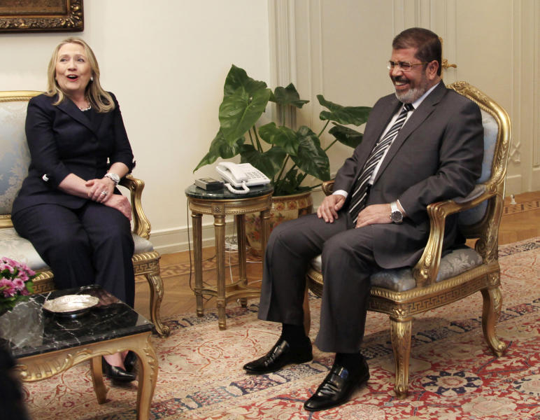 FILE - This July 14, 2012 file photo shows Secretary of State Hillary Rodham Clinton and Egyptian President Mohammed Morsi laugh during a photo opportunity at their meeting at the Presidential palace in Cairo, Egypt. The US has been here before with Egypt, praising its leader for championing Israeli-Palestinian peace efforts while expressing deep concern over his commitment to democracy at home. But with options limited, the Obama administration is keeping its faith in President Mohammed Morsi. (AP Photo/Maya Alleruzzo, File)