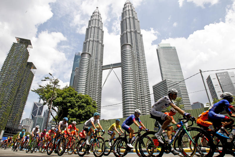 FILE - In this March 25, 2018 file photo, cyclists move past Malaysia's landmark Petronas Twin Towers during the last stage of Le Tour de Langkawi cycling race in Kuala Lumpur, Malaysia. Architect César Pelli, renowned for designing some of the world's tallest buildings, including the Petronas Twin Towers, has died, Friday, July 19, 2019,  his firm said.  (AP Photo/Sadiq Asyraf, File)