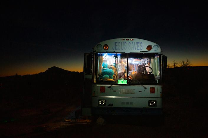 """Paula and Max's 'Jesus Saves' bus provides warmth on cold desert nights outside Lake Havasu City, Az., on Feb. 23. Paula was raised Jewish and does not identify as Christian; she found the retired Baptist school bus in San Diego last year and it fit within her budget.<span class=""""copyright"""">Nina Riggio for TIME</span>"""