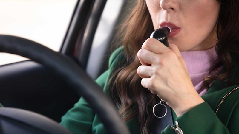 Woman using alcohol breathalyser in the car