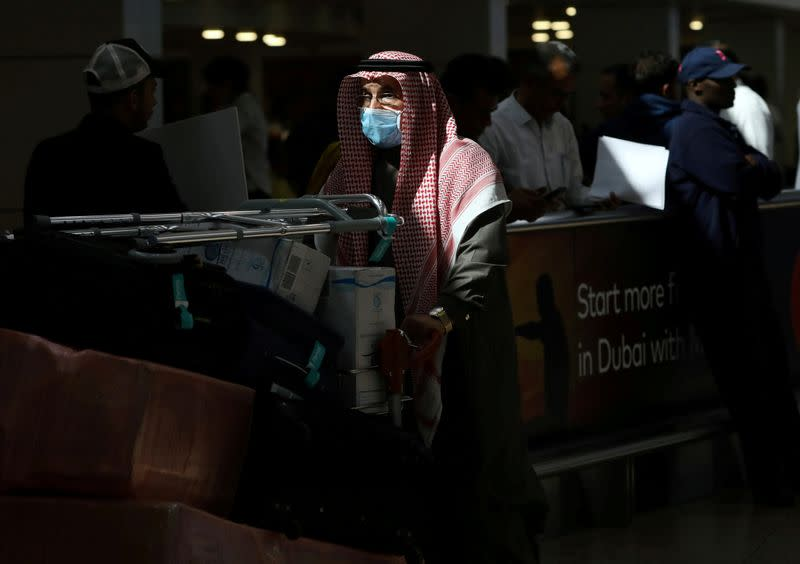 A traveller wears a mask as he pushes a cart with luggage at Dubai International Airport, after the UAE's Ministry of Health and Community Prevention confirmed the country's first case of coronavirus, in Dubai