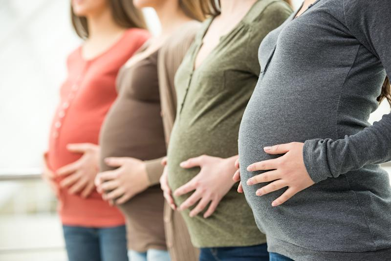 Side view of three pregnant women are touching their bellies with hands. Maternity concept.