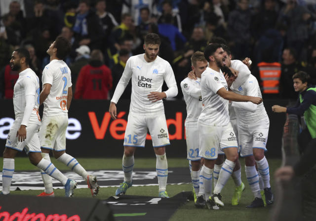 Marseille players celebrate after Marseille's Nemanja Radonjic scored his side's second goal during the French League One soccer match between Marseille and Brest at the Velodrome stadium in Marseille, southern France, Friday, Nov. 29, 2019. (AP Photo/Daniel Cole)