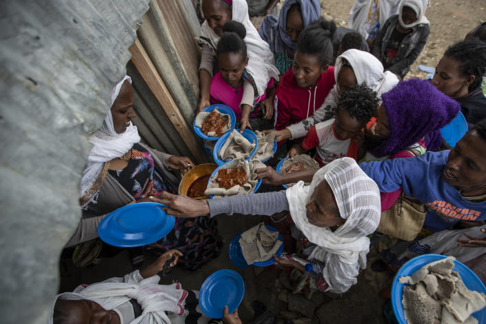 Displaced Tigrayans line up to receive food donated by local residents at a reception center for the internally displaced in Mekele, in the Tigray region of northern Ethiopia, on Sunday, May 9, 2021. In war-torn Tigray, more than 350,000 people already face famine, according to the U.N. and other humanitarian groups. It is not just that people are starving; it is that many are being starved, The Associated Press found. (AP Photo/Ben Curtis)