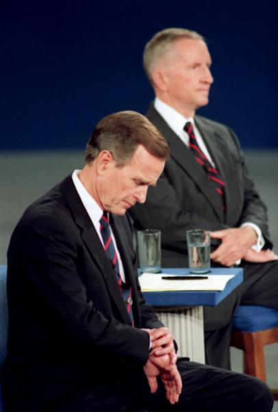 FILE - In this Oct. 15, 1992, file photo President George H.W. Bush looks at his watch during the 1992 presidential campaign debate with other candidates, Independent Ross Perot, top, and Democrat Bill Clinton, not shown, at the University of Richmond, Va. Finally, the fall season delivers the matchup Americans have been waiting for, President Barack Obama goes one-on-one with Republican Mitt Romney in three prime-time debates. With the race a dead heat, the debates take on an oversized role in the few weeks between now and Election Day. One small mistake or impression _ a glance at a watch, repetitive sighing _ could roil the campaign for days and linger in voters' mind. This is especially true for two polished candidates who will have the soundbites and rhetoric down cool. (AP Photo/Ron Edmonds, File)