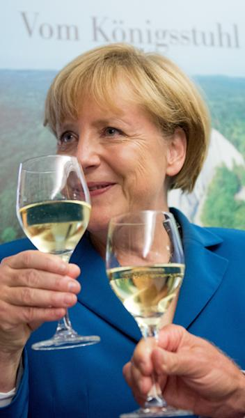 German Chancellor Angela Merkel, chairwoman of the Christian Democratic party CDU drinks a glass of withe wine at the party headquarters after the national elections in Berlin Sunday, Sept. 22, 2013. Chancellor Angela Merkel's conservatives triumphed in Germany's election Sunday, and could even win the first single party majority in more than 50 years. Her center-right coalition partners risked ejection from parliament for the first time in their post-World War II history.(AP Photo/dpa,Julian Stratenschulte)