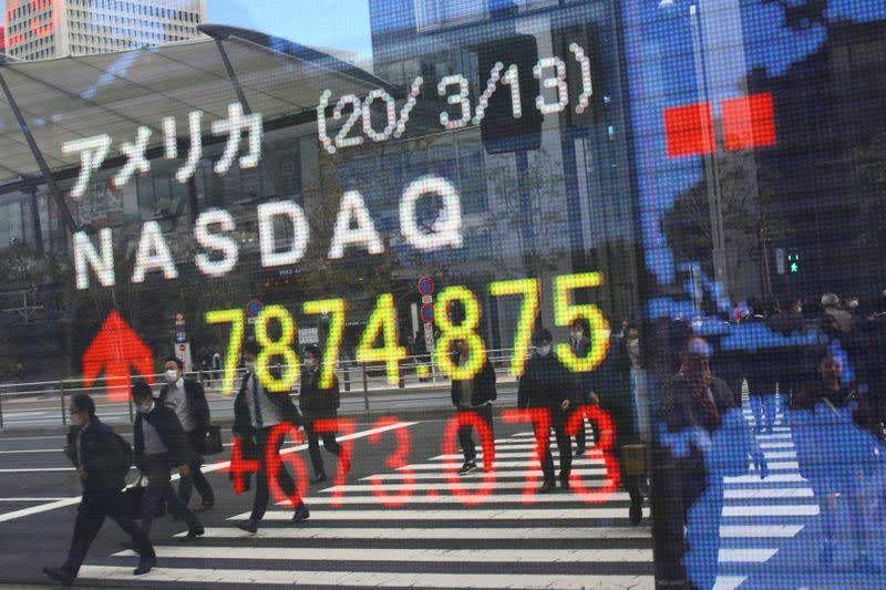 People wear protective face masks as they are reflected in a stock quotation board outside a brokerage in Tokyo