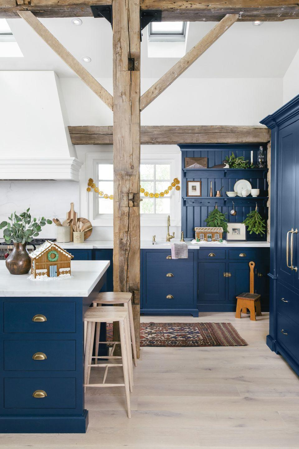 <p>Peg rail-lined shelves are the ideal spot to hang evergreen branches, while a simple garland adds contrast to the window. The sprawling central island is perfectly sized for baking pursuits, including a gingerbread barn. </p>