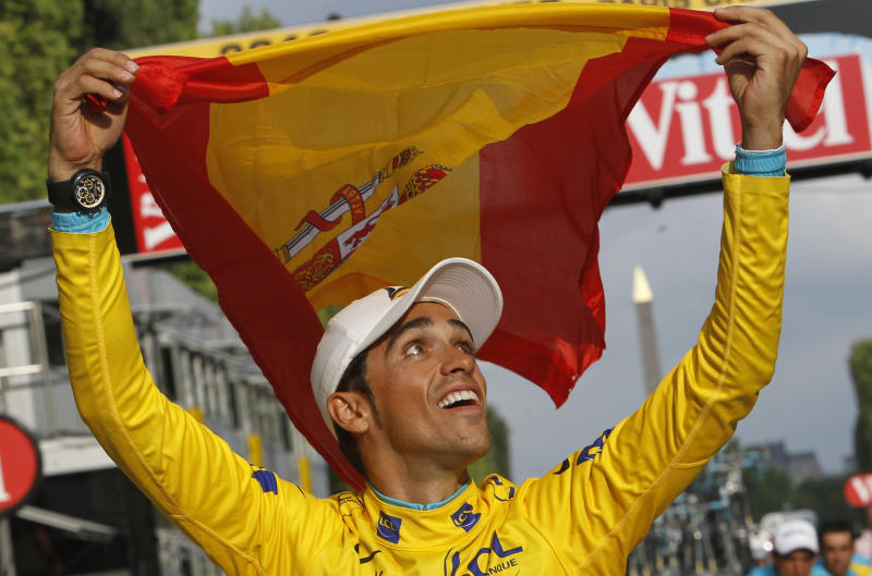 FILE - in this July 25, 2010 file photo,  three-time Tour de France winner Alberto Contador of Spain holds aloft the Spanish national flag during a victory lap  after winning the Tour de France cycling race in Paris. he court of a Arbitration for Sport delivered the verdict Monday, 17 months after Contador returned a positive drug test in winning the 2010 Tour de France race. Contador has always claimed the positive result was from contaminated beef he eat during the race. (AP Photo/Christophe Ena, File)