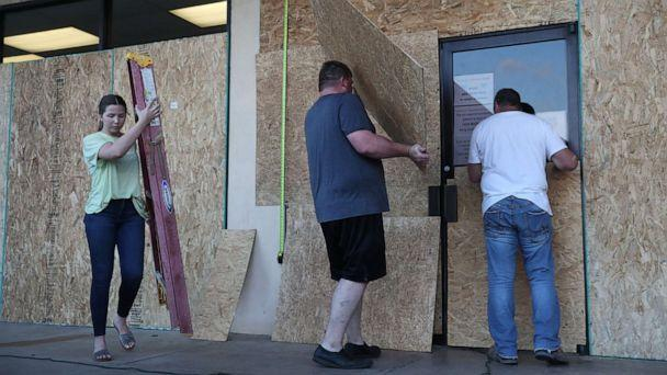 PHOTO: LAKE CHARLES, LOUISIANA- AUGUST 25: (L-R) Lacey Buller, Tyler Arnold and Mike Buller work on placing plywood over the windows of their business before the arrival of Hurricane Laura on August 25, 2020 in Lake Charles, Louisiana. (Joe Raedle/Getty Images)