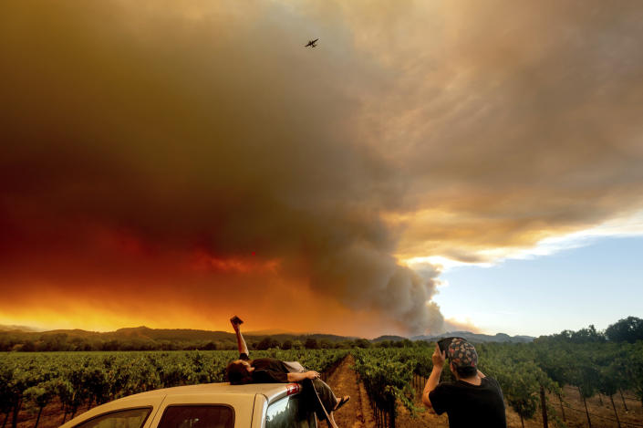 FILE - In this Aug. 20, 2020, file photo, Thomas Henney, left, and Charles Chavira watch a plume spread over Healdsburg, Calif., as the LNU Lightning Complex fires burn. Two unusual weather phenomena combined to create some of the most destructive wildfires the West Coast states have seen in modern times. (AP Photo/Noah Berger, File)