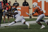 West Virginia's Bryce Ford-Wheaton (0) reaches in vain for a pass as Texas' Josh Thompson (9) defends during the second half of an NCAA college football game in Austin, Texas, Saturday, Nov. 7, 2020. (AP Photo/Chuck Burton)