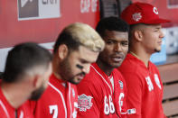 Cincinnati Reds right fielder Yasiel Puig (66) sits with his teammates in the dugout in the second inning of a baseball game against the Miami Marlins, Thursday, April 11, 2019, in Cincinnati. (AP Photo/John Minchillo)