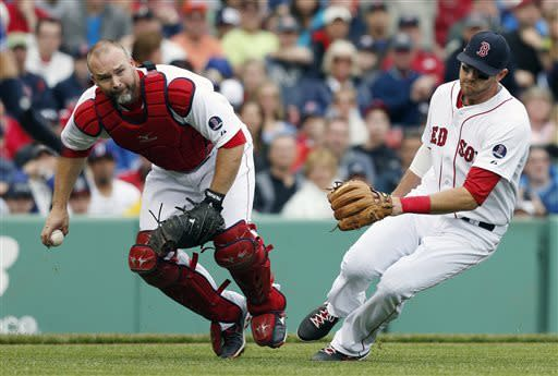 Boston Red Sox's David Ross, left, fields the ball next to teammate Will Middlebrooks on a sacrifice bunt by Toronto Blue Jays' Munenori Kawasaki in the third inning of a baseball game in Boston, Saturday, May 11, 2013. Kawasaki was out at first. (AP Photo/Michael Dwyer)