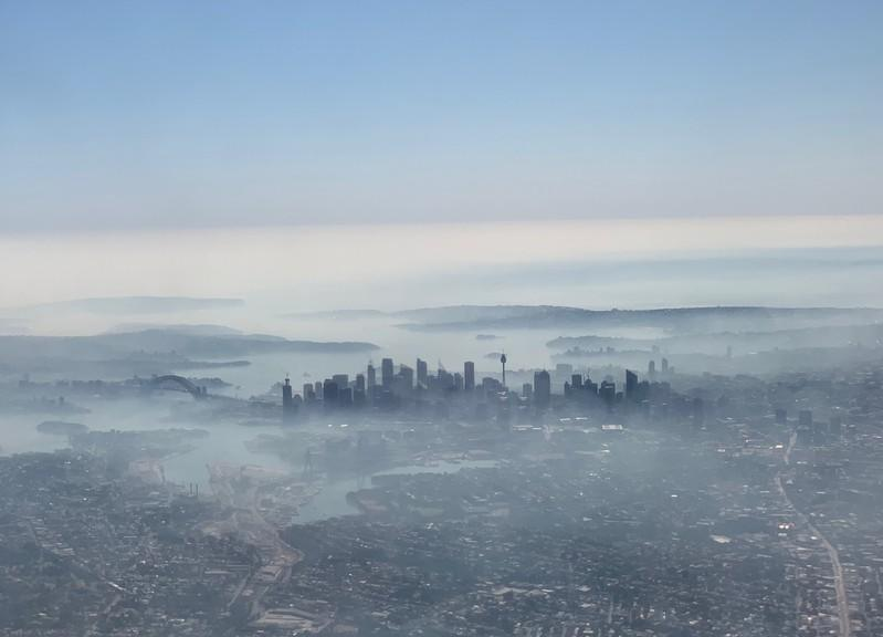 An image taken on a smart phone from a plane window shows smoke haze blanketing Sydney