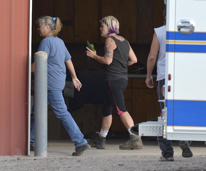 In this photo provided by the Imperial Republican, kidnapping victim Julie Hanes, 38, of Lincoln, Neb., walks into a police staging area after being released by her estranged husband who abducted her, following a massive manhunt for the pair, Sunday, Aug. 25, 2013, near Imperial, Neb. Hanes' husband shot and killed himself after releasing his wife. (AP Photo/Imperial Republican, Russ Pankonin)