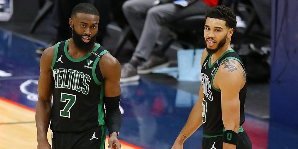 Jaylen Brown and Jayson Tatum stand side by side, smiling during a game.