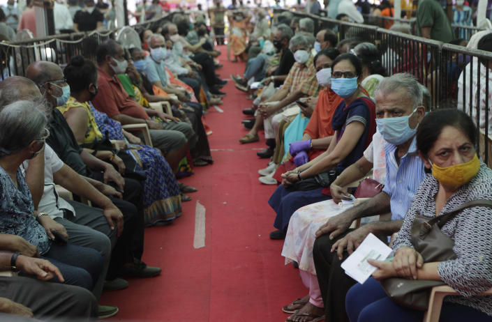 People wait to receive COVID-19 vaccine in Mumbai, India, Thursday, April 29, 2021. India set another global record in new virus cases Thursday, as millions of people in one state cast votes despite rising infections and the country geared up to open its vaccination rollout to all adults amid snags. (AP Photo/Rajanish Kakade)