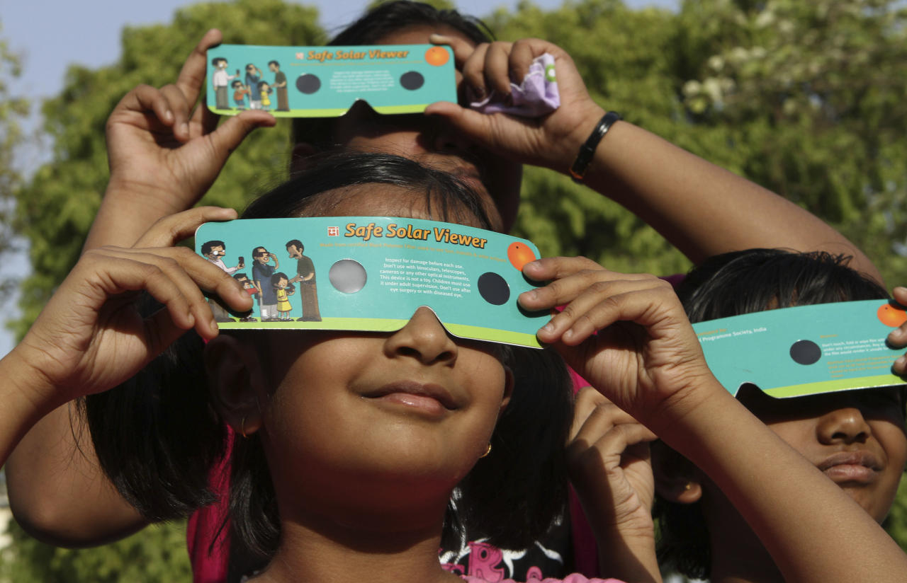 Indian children use cardboard eclipse glasses as they prepare to watch the transit of Venus in Allahabad, India, Tuesday, June 5, 2012. Stargazers around the world are setting up special telescopes and passing out cardboard eclipse glasses to view the once-in-a-lifetime celestial cameo of Venus passing in front of the sun. Venus is Earth's second-closest neighboring planet. (AP Photo/Rajesh Kumar Singh)