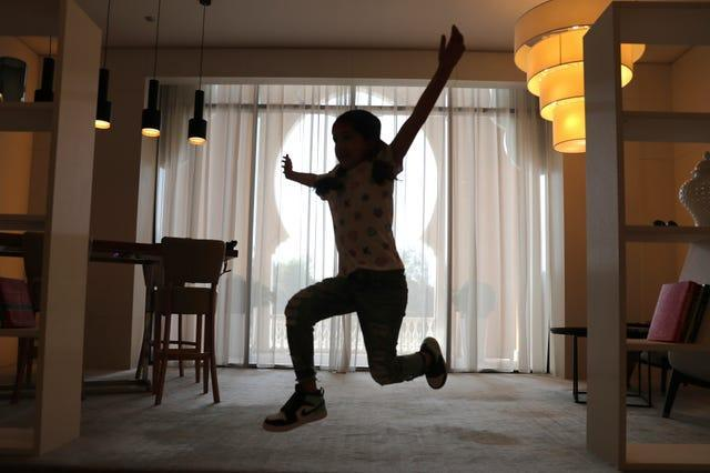 Michelle Rasul jumps around in the lobby of her apartment building in Dubai, United Arab Emirates