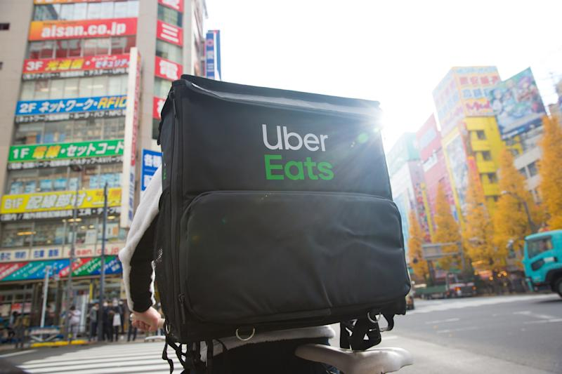 TOKYO, JAPAN - 2019/12/18: An Uber Eats cyclist rides through Chuo-dori Avenue cross road in Akihabara, Tokyo. Akihabara, also called Akiba after a former local shrine, is a district in central Tokyo that is famous for its many electronics shops. In more recent years, Akihabara has gained recognition as the center of Japan's otaku (diehard fan) culture, and many shops and establishments devoted to anime and manga are now dispersed among the electronic stores in the district. (Photo by Stanislav Kogiku/SOPA Images/LightRocket via Getty Images)