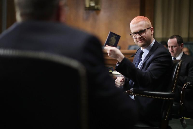 Former director of research for Cambridge Analytica Christopher Wylie pulls out his Canadian passport before testifying to a Senate Judiciary Committee hearing (AFP Photo/CHIP SOMODEVILLA)