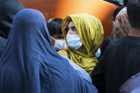 Families evacuated from Kabul, Afghanistan, wait to board a bus after they arrived at Washington Dulles International Airport, in Chantilly, Va., on Wednesday, Aug. 25, 2021. (AP Photo/Jose Luis Magana)
