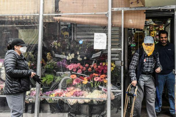 PHOTO: A worker controls the flow of customers through a door in a bodega on April 29, 2020 in New York City. (Stephanie Keith/Getty Images)